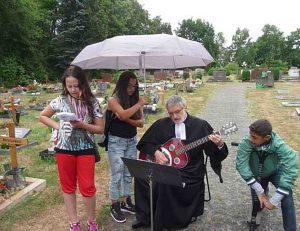 Pfarrer Schütz begleitet ein Lied mit der Gitarre, beschirmt von einer Konfirmandin