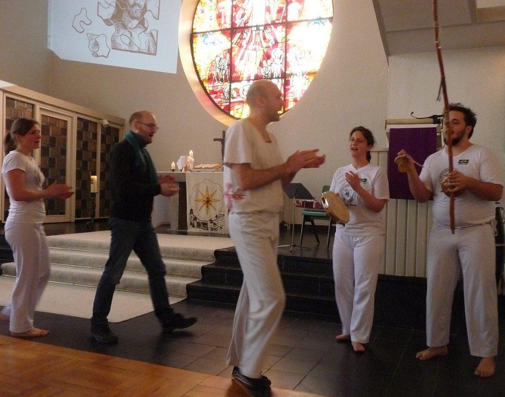 Die Capoeira-Gruppe stellt sich vorne rechts vor dem Altarraum auf, wo die Stühle weggeräumt sind