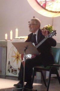 Pfarrer Schütz begleitet ein Lied mit seiner Gitarre