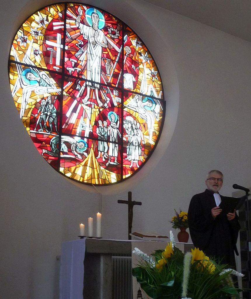 Pfarrer Helmut Schütz am Altar vor dem Fensterbild von Claus Wallner