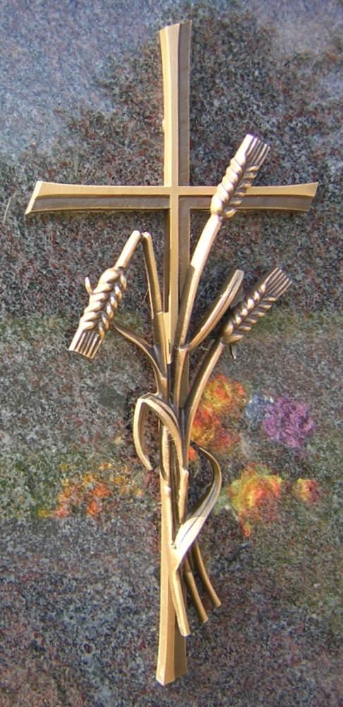 Ein Kreuz auf einem Grabstein mit drei Ähren, eine davon abgeknickt.