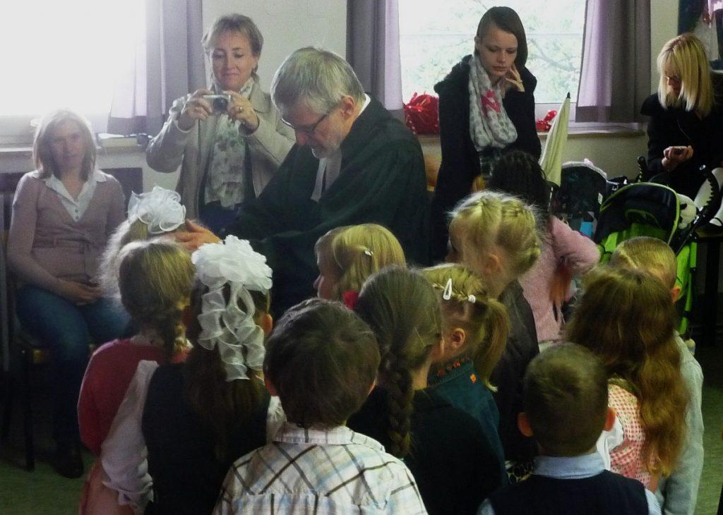 Die christlichen Schulkinder werden von Pfarrer Schütz mit Handauflegung gesegnet