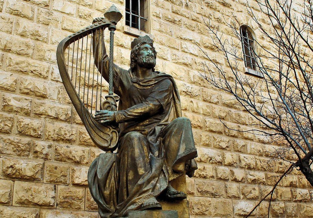 Bronzeskulptur vor einer Mauer: König David mit seiner Harfe
