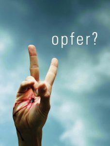 """Eine durchbohrte Hand macht das Siegeszeichen vor einem bewölkten Himmel - darüber ist das Wort """"opfer?"""" zu sehen"""