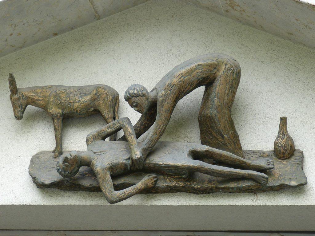 Bronzeskulptur eines liegenden Mannes, über den sich der barmherzige Samariter beugt, daneben steht sein Esel und eine Ölflasche
