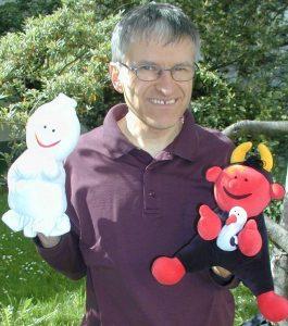 Pfarrer Schütz mit den Handpuppen Gabi (die aussieht wie ein kleines Gespenst und ein Engel ist), Lutz (der aussieht wie ein rotes Teufelchen) und Fischli (der ein Fingerpuppen-Pinguin ist).