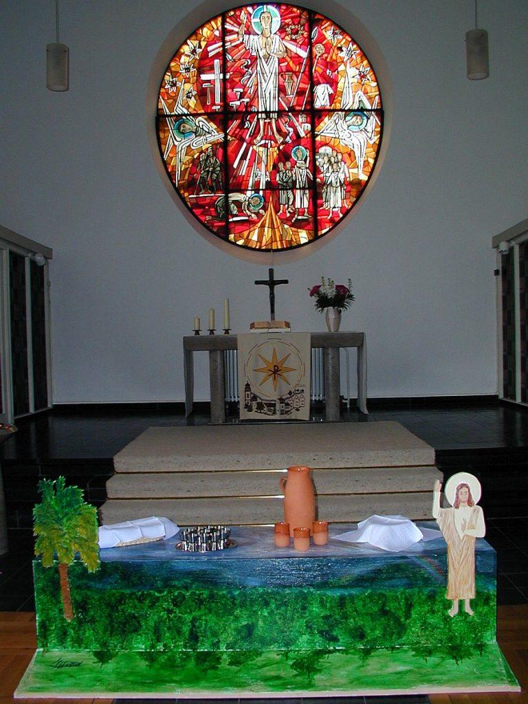 Die ART-Bank mit dem segnenden Jesus und einer Palme, auf der alles zum Abendmahl bereitet ist, vor dem Altarfenster der Pauluskirche