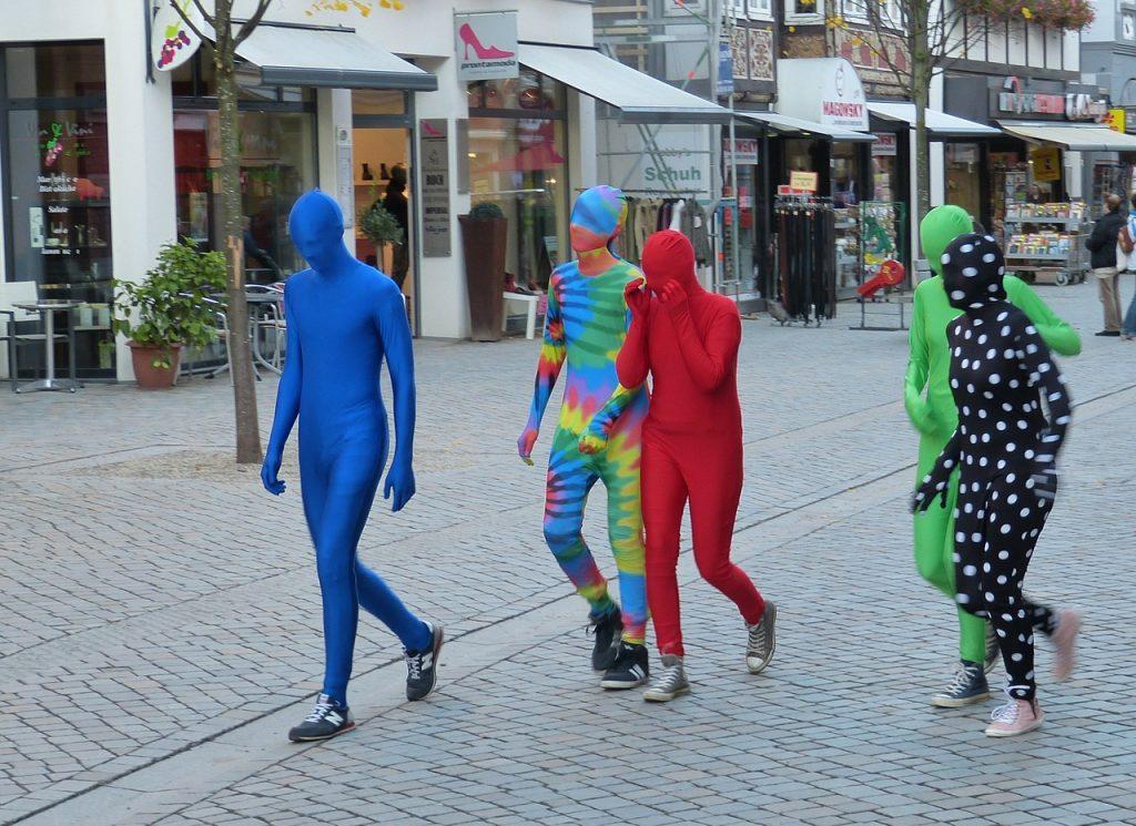 Männer, die in bunte Ganzkörperkleider verkleidet sind, wobei auch das Gesicht bedeckt ist