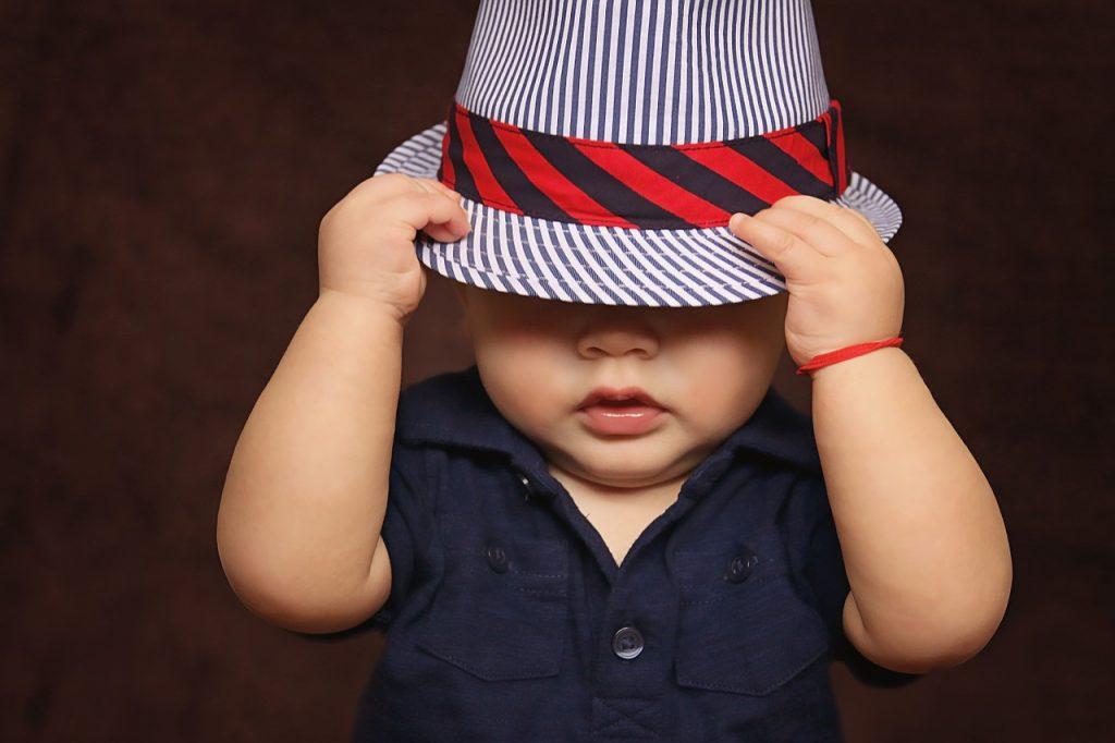 Kleines Kind, das sich einen Hut ins Gesicht zieht