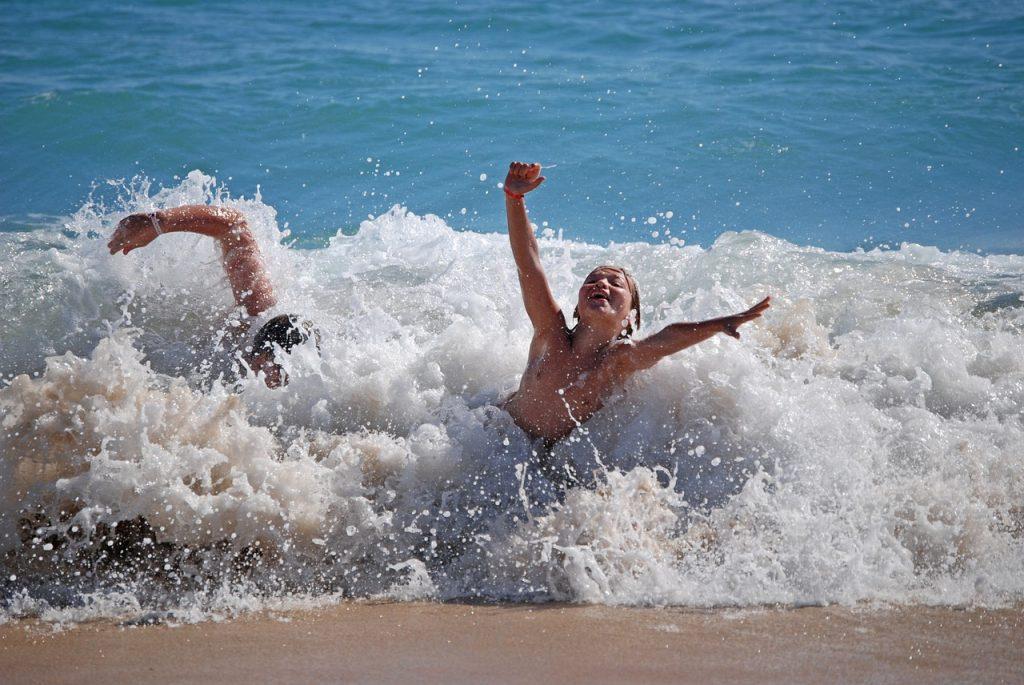 Zwei Jungs kraulen und springen durch die letzte Welle an den Strand