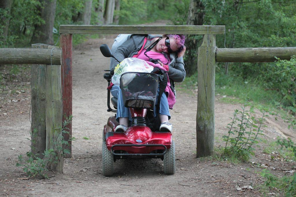 Frau im Rollstuhl bückt sich unter einer Barriere auf einem Waldweg hindurch