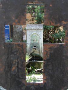Durchblick durch ein Kreuz auf einen Brunnen