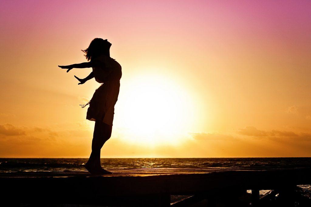 Die Silhouette einer ihr Gesicht glücklich in den Himmel streckenden Frau vor Sonnenaufgang