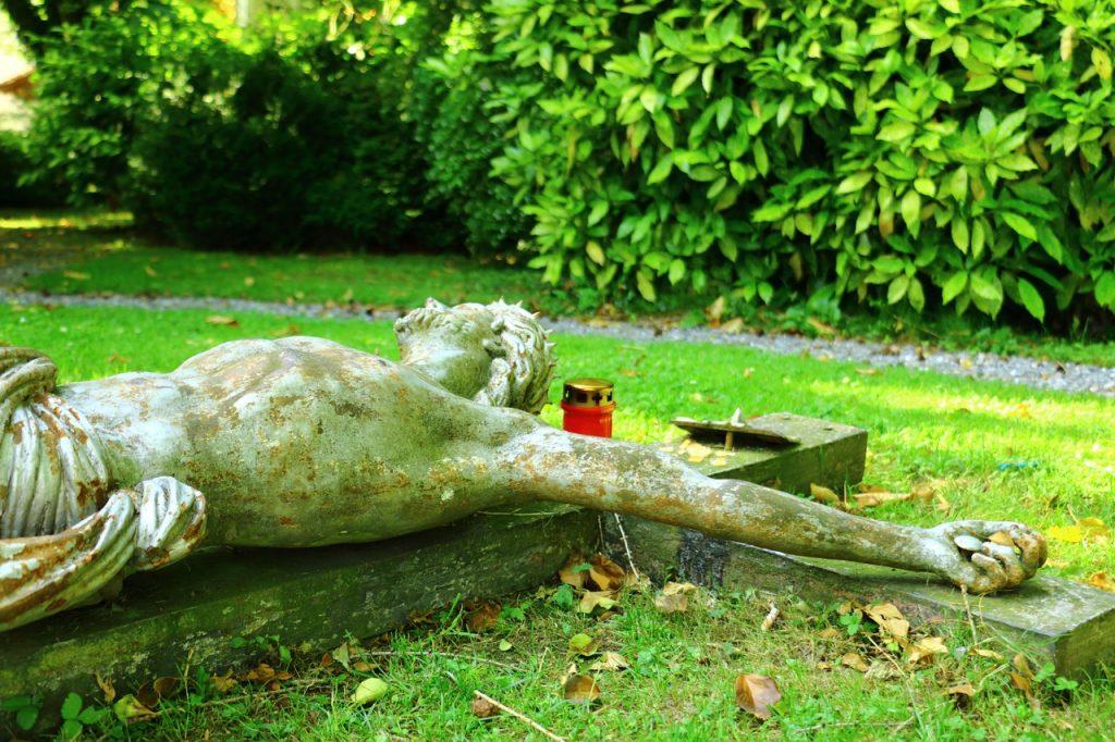 Man sieht den gekreuzigten Jesus an einem Kreuz, das auf dem Boden im Garten liegt