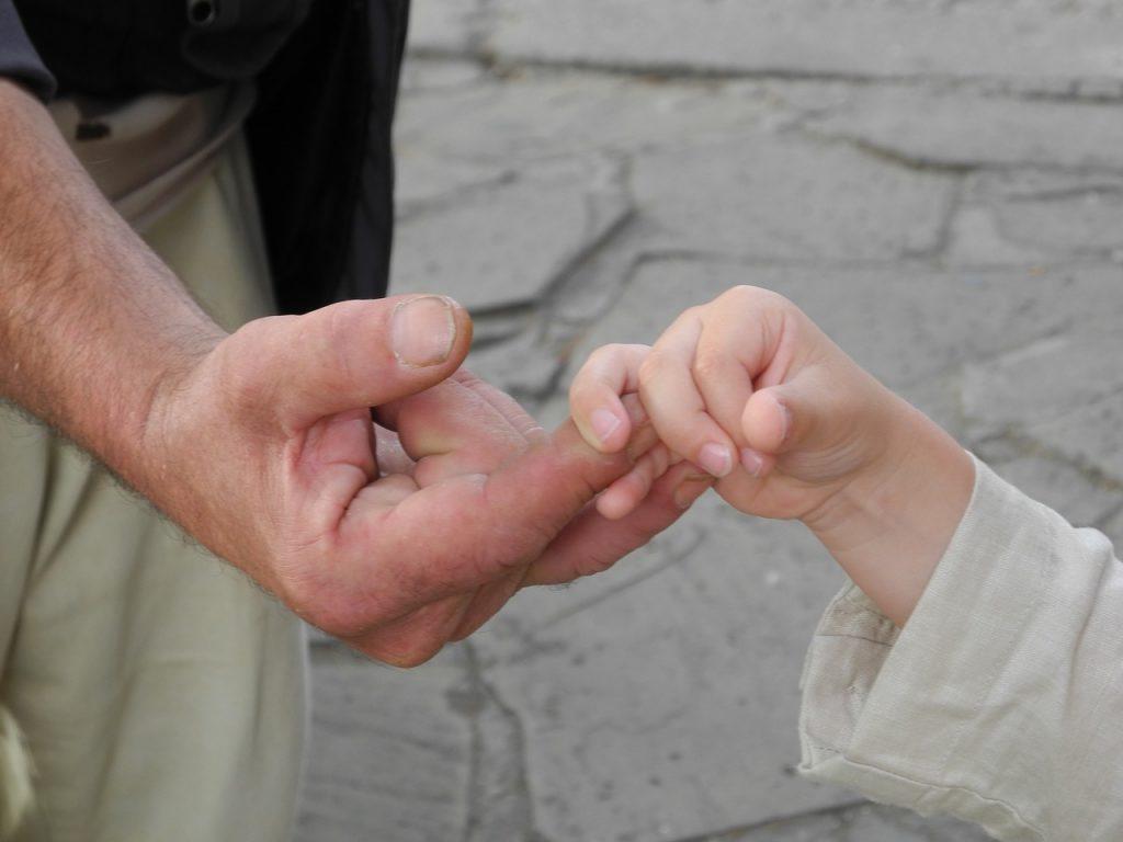 Eine Kinderhand fasst die Finger der Hand eines älteren Menschen