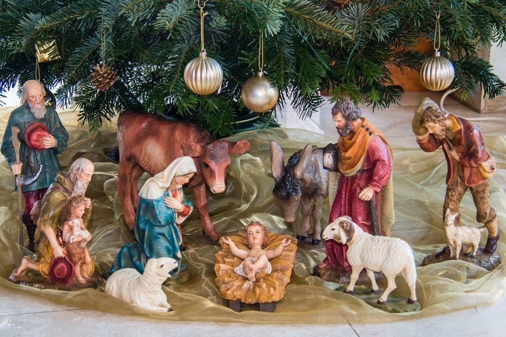 Eine Weihnachtskrippe unter dem Christbaum mit der Heiligen Familie und Hirten und Schafen