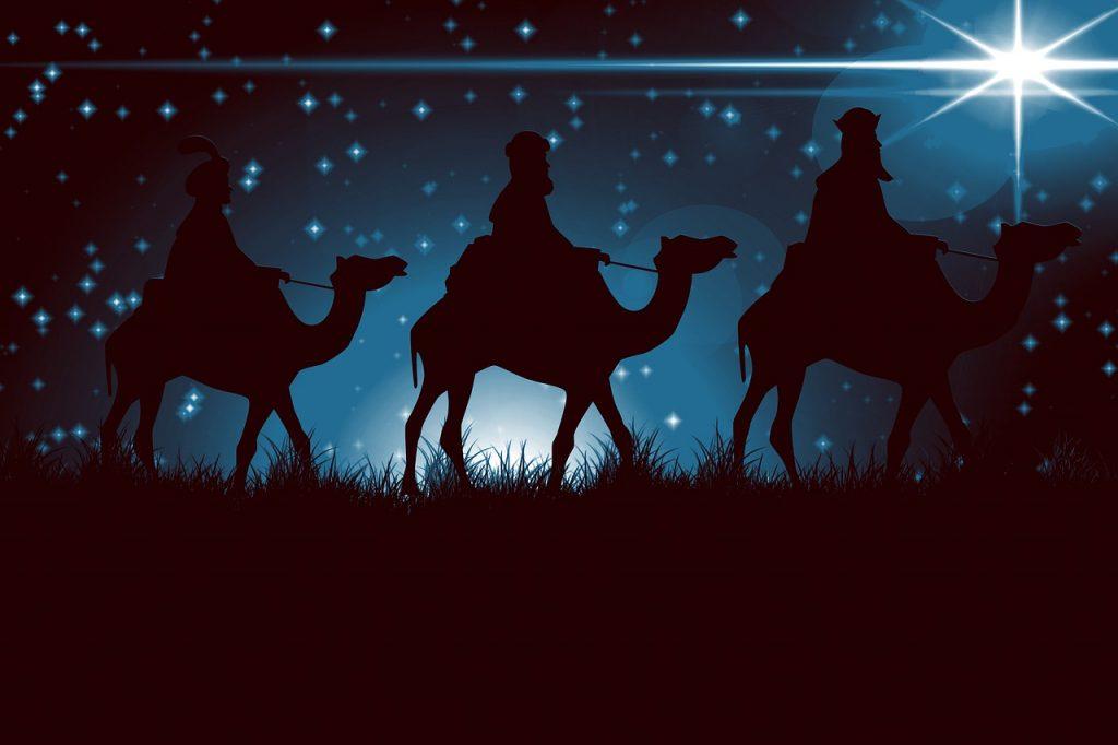 Die Heiligen Drei Könige auf Kamelen vor einem Sternenhimmel mit einem sehr hell leuchtenden Stern