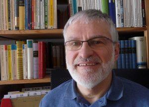Helmut Schütz vor einem Bücherregal