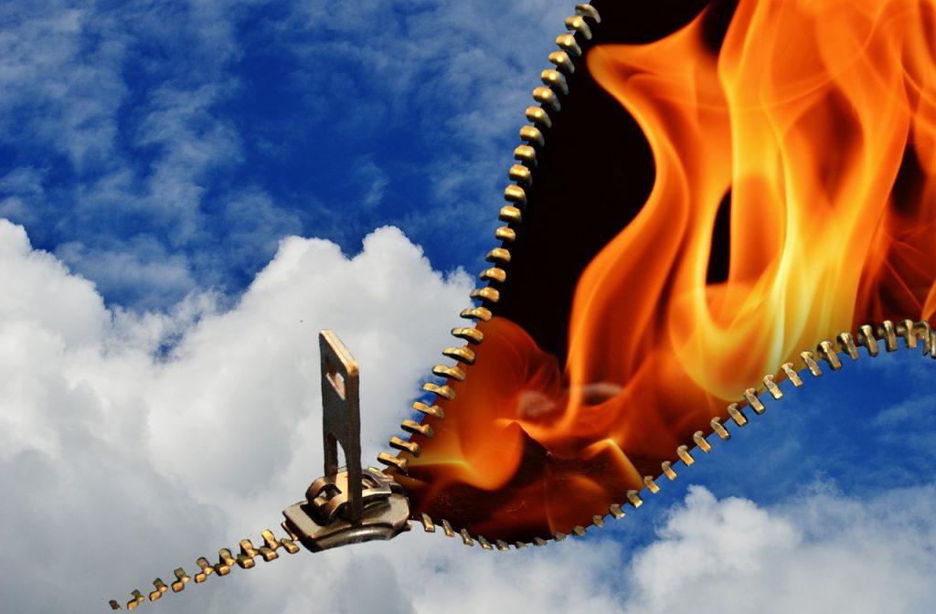 Ein Reißverschluss öffnet den blauen Wolkenhimmel, hinter dem Feuer zu sehen ist