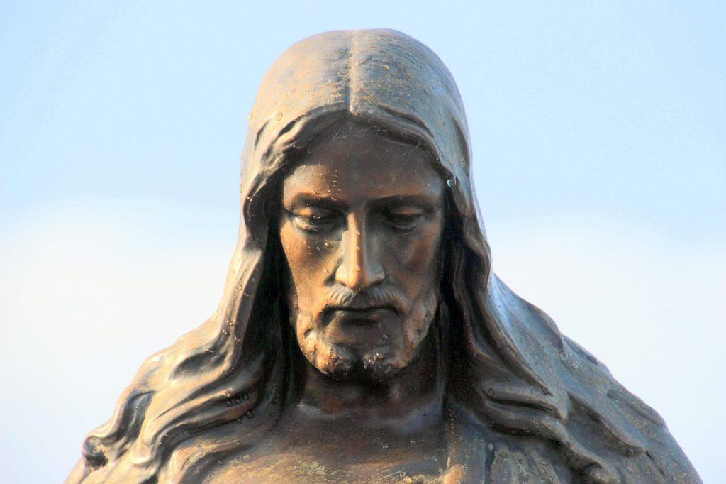 Jesus-Skulptur mit einem ernsten gesenkten Gesicht, mit Regentropfen bedeckt