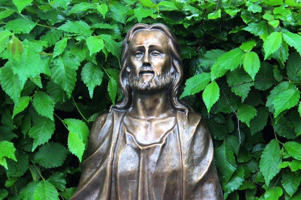 Jesus-Statue, von grünen Blättern umgeben