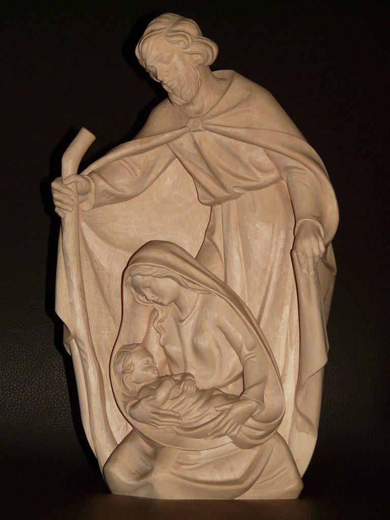 Holzschnitzerei: Josef steht hinter Maria, die ihr Kind Jesus im Arm hält