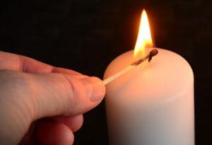 Eine Kerze wird mit einem Zündholz angezündet