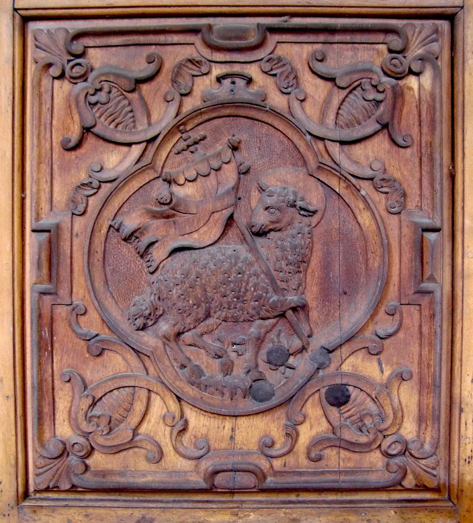 Das siegreiche Lamm Gottes als Schnitzerei an einer Kirchenbank