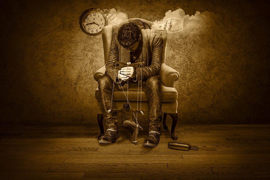 Ein Mann hockt auf einem Sessel und hält eine Figur, die wie er selbst aussieht, an Marionettenfäden