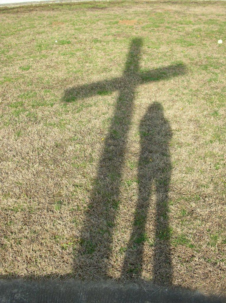 Der Schatten eines Kreuzes, daneben der eines Menschen