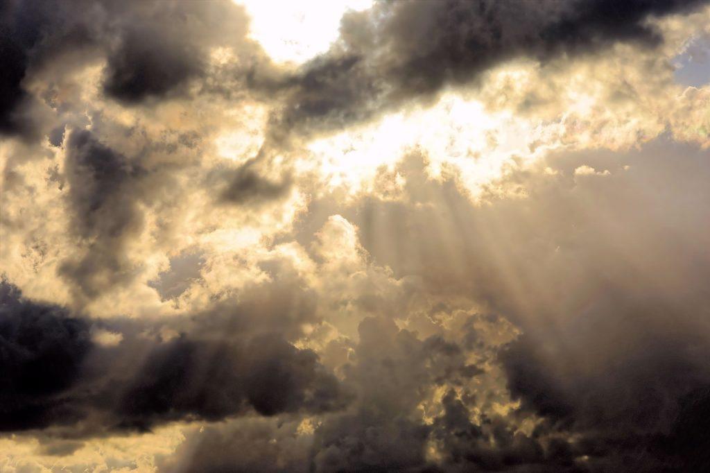 Sonnenlicht fällt durch helle und dunkle Wolken