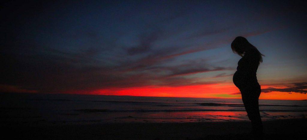Die Silhouette einer schwangeren Frau vor dem Sonnenuntergang