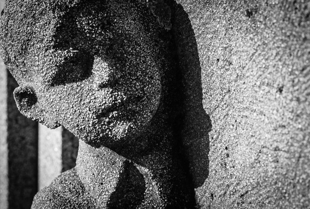 Statue eines Jungen an einem Grabstein