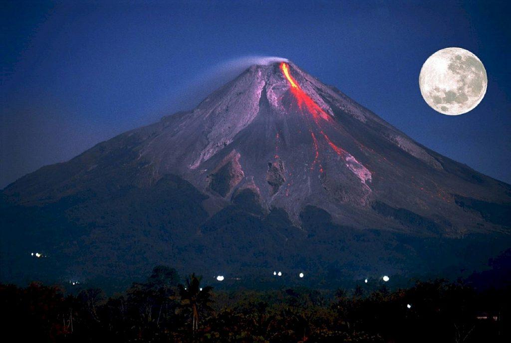 Der Vulkan Merapi in Indonesien - mit roter Lava vor einem großen Vollmond