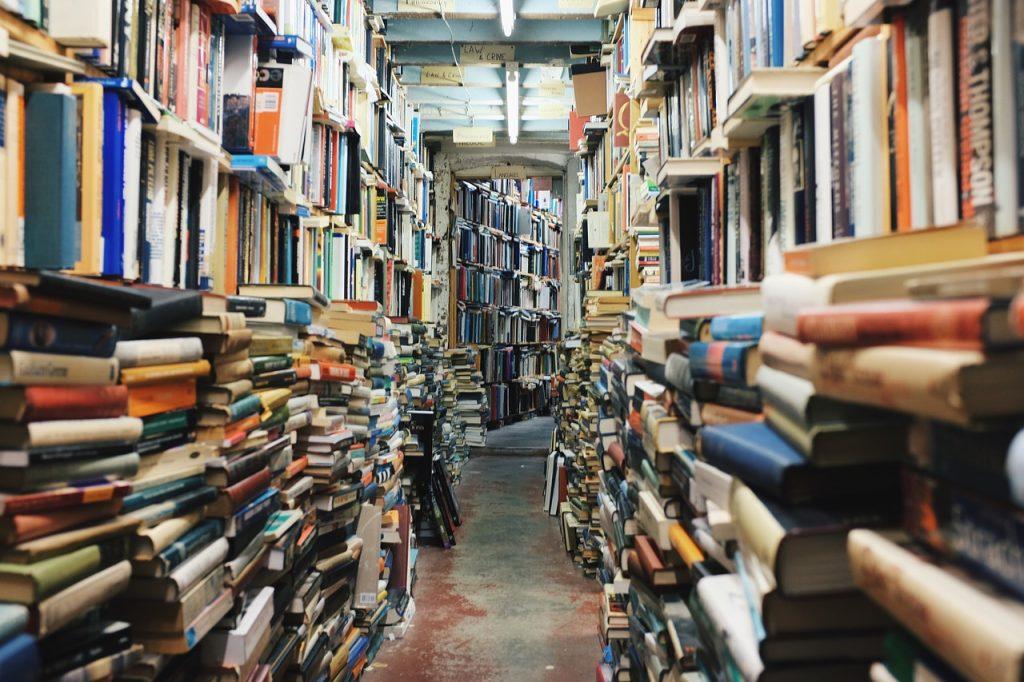 Voll gestopfte Bücherregale und Bücherstapel mit engem Gang dazwischen