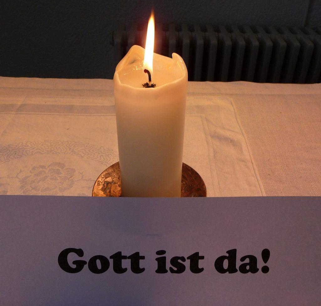 "Kerze auf dem Altar der Pauluskirche mit dem Schriftzug ""Gott ist da!"""