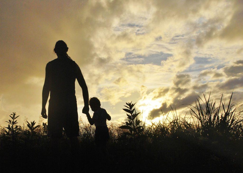 Ein Junge an der Hand des Vaters vor bewölktem Himmel, durch die Wolken scheint aber die Sonne