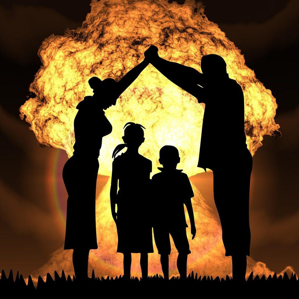 Schattenriss eines Elternpaares, das ihre beiden Kinder beschützt, vor einem Atompilz