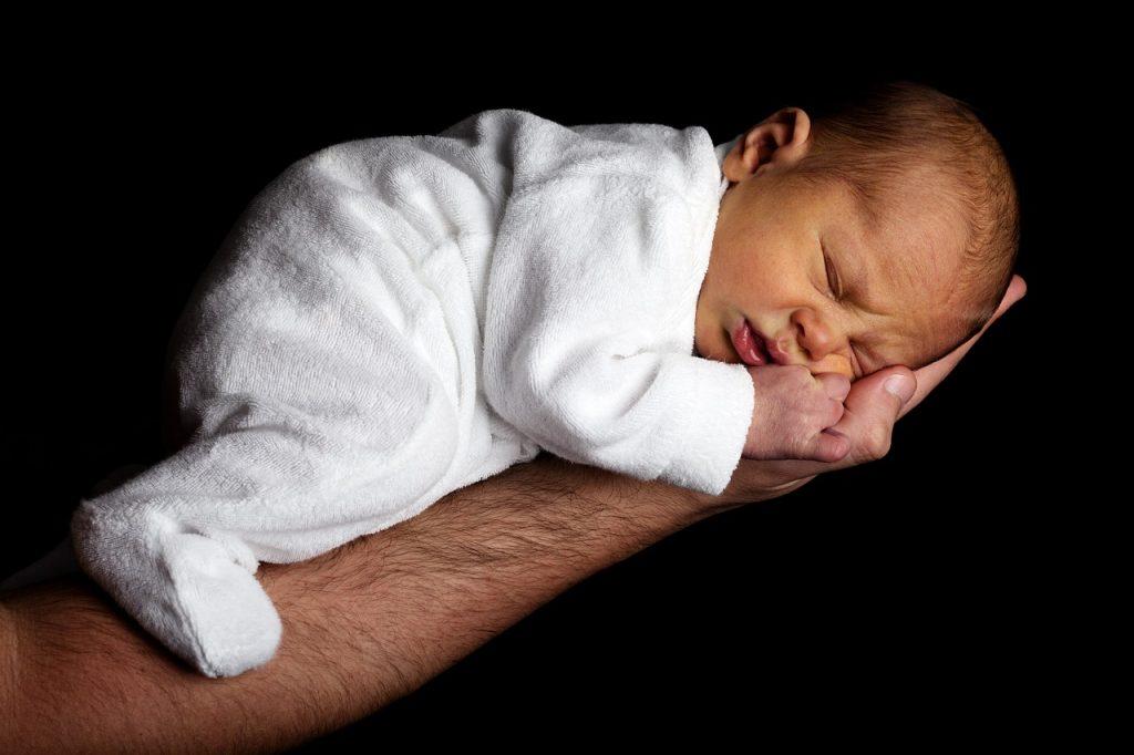 Ein neugeborenes Baby auf dem Arm des Vaters