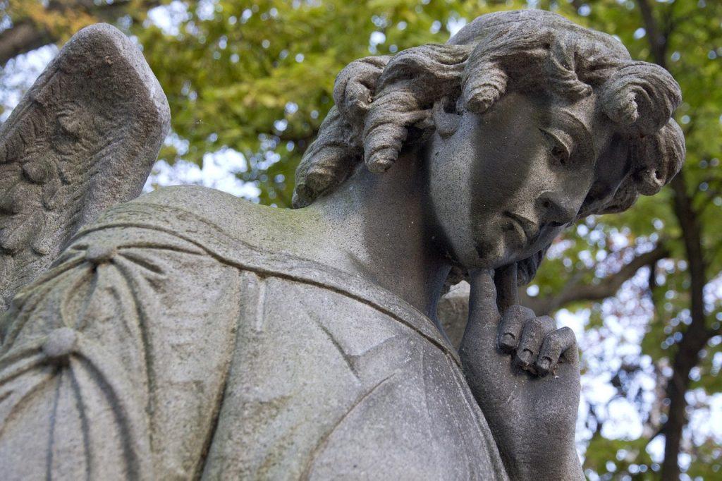 Engel-Skulptur aus Stein, nachdenklich, weiblich, mit dem Finger am Kinn