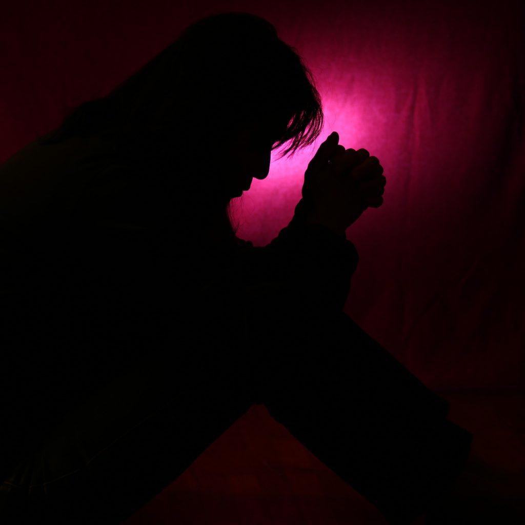 Ein betender Mann im Dunkeln vor violettem Licht