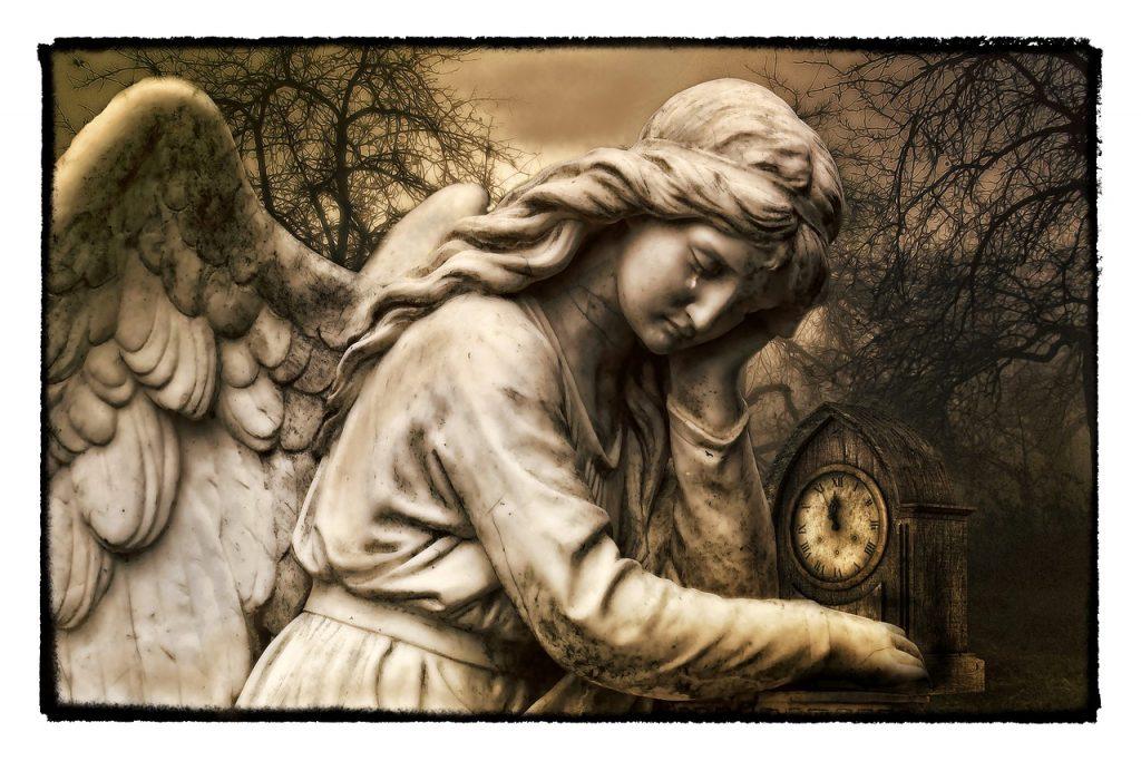 Weinender Engel (Steinfigur) mit Uhr kurz vor Mitternacht