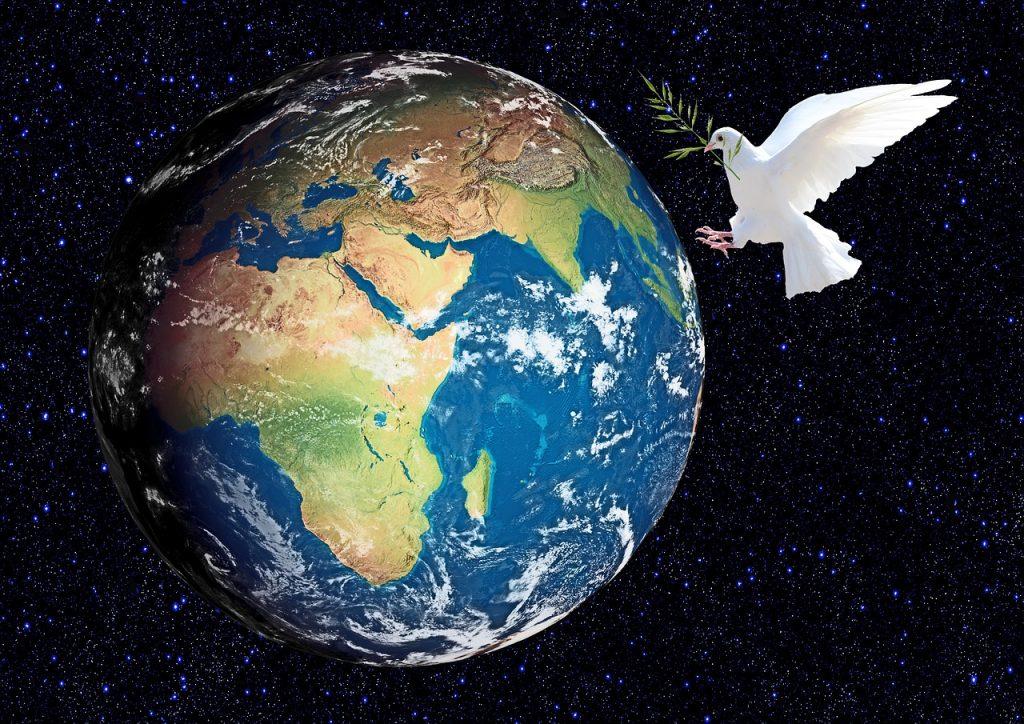 Eine Friedenstaube mit Ölzweig im Schnabel fliegt einen Globus an