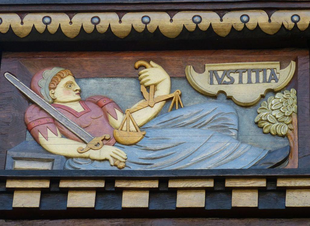 Symbol der Gerechtigkeit - eine Frau, die sich ausruht, mit dem Schwert in der rechten und der Waage in der linken Hand