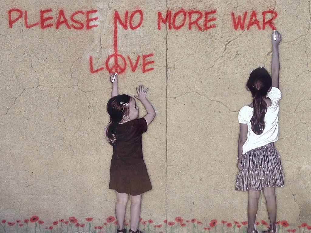 """Graffiti von zwei kleinen Mädchen für den Frieden: """"Please no more war"""" und """"Love"""" mit dem Peace-Zeichen als """"o"""""""