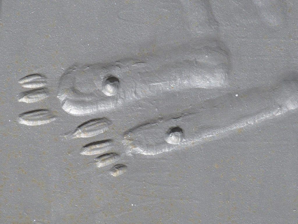 Jesu durchbohrte Füße (stilisiert) an einem Kirchenportal in Heilbronn
