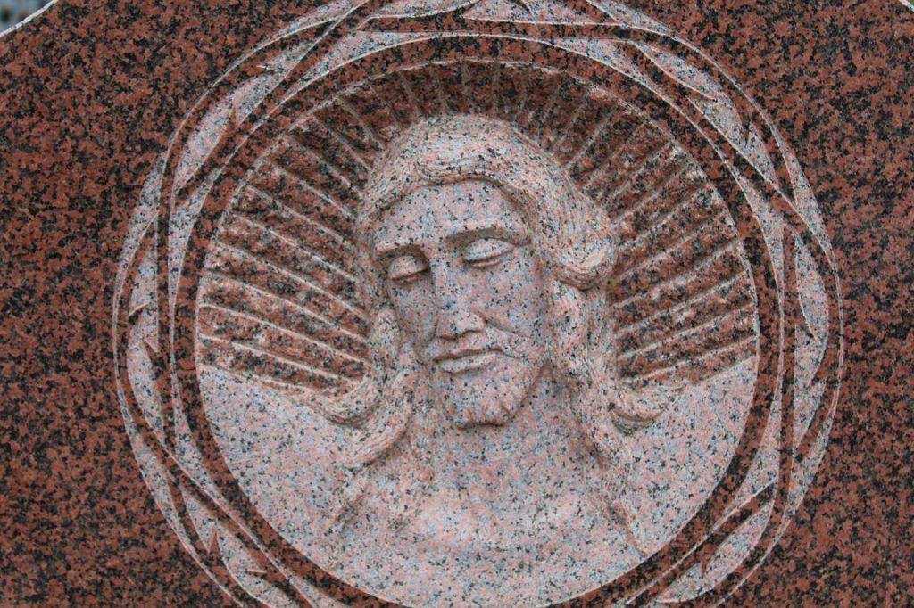 Jesu Gesicht auf einem Grabstein