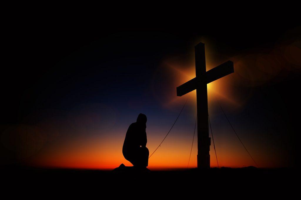 Kniender Mensch vor dem Kreuz
