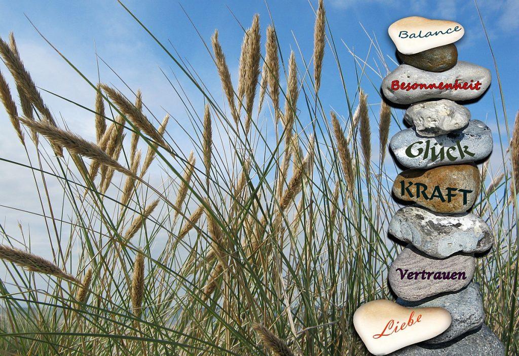 Steine im Gras aufeinandergestapelt mit Aufschriften: Balance, Besonnenheit, Glück, Kraft, Vertrauen, Liebe