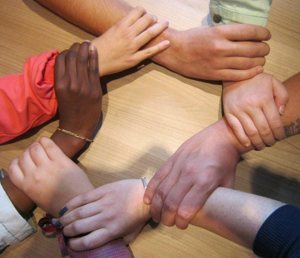 Ein Kreis von Händen, die einander anfassen, in verschiedenen Hautfarben